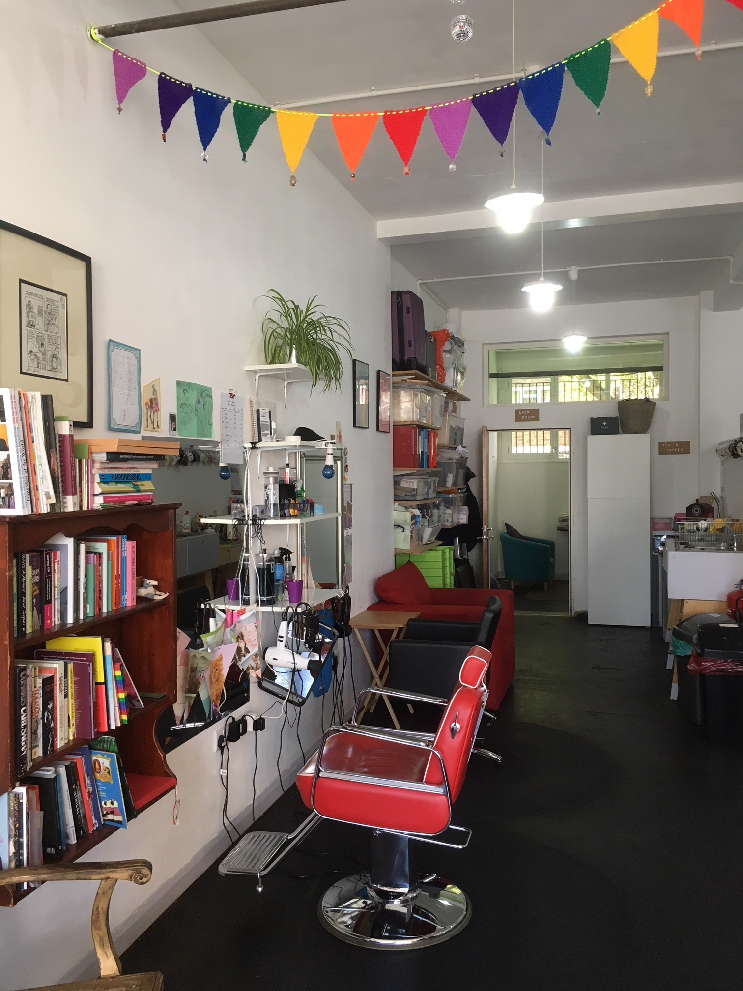Photo of the inside of a barber shop, including a red barbers chair, rainbow flag garland, and a bookcase filled with books.