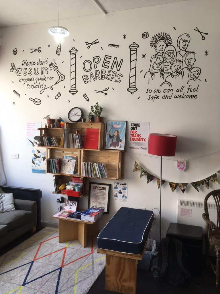 The inside of the Open Barbers salon, featuring the zine library and seating
