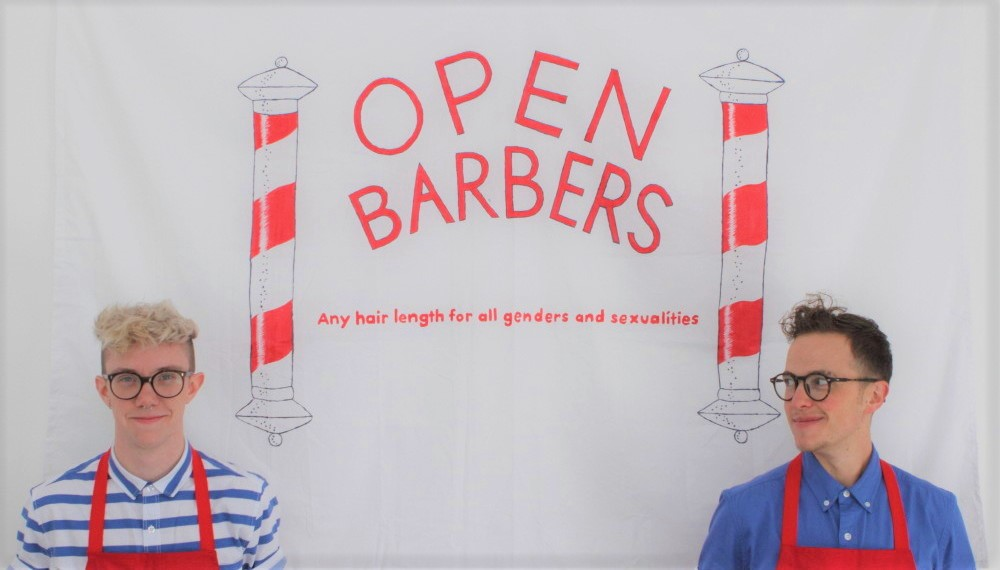 Felix and Grey in front of an Open Barbers banner