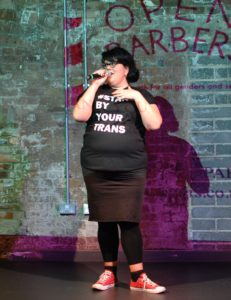 Amy Lamé is standing infront of a brick wall which has a cropped part of the Open Barbers logo projected on it. Amy is wearing red converse trainers, black socks, black leggings, a black skirt and a black tshirt which says #stand by your trans in white. Amy is speaking into a microphone. Amy has black hair and glasses.