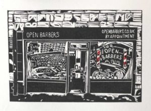 A black and white lino print of the shop front of Open Barbers. The barbers poles in the Open Barbers logo on the window are red and white, the only part of the print with colour. The shop front signage says Open Barbers on the left and openbarbers.co.uk on the right, with by appointment written underneath. The logo on the window includes the words Open Barbers. The windows capture reflections from the street inncluding brick buildings, a car and a bicycle.