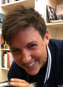 Meg-John Barkers is leaning forward infront of a bookshelf. Meg-John has short brown hair and is smiling. Meg-John is wearing a navy blue top with white stripes at the collar.