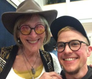 Kate Bornstein is standing next to Greygory Vass with a hand on Greygory's shoulder. They are in a room that has blue and white interior. Kate is wearing a brown hat and glasses with a tint that fades from pink to yellow. Katie is wearing two necklaces and a white top with a yellow top underneath, and a brown, black and white patterned waistcoat. Kate has blonde bobbed hair with a fringe and is smiling. Greygory is wearing a blue baseball cap and has short blonde hair and dark rimmed glasses. Greygory is smiling and has a bearded chin and a dark top.