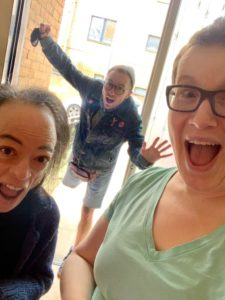 Liz Carr (left) and Jo Church (right) are in the foreground and Greygory Vass is falling through the open door in the background. Liz has dark hair and is wearing a navy blue top.  Jo has short, brown hair, is wearing a grean v neck t-shirt and dark rimmed glasses. Both Liz and Jo have open mouths and excited expression. Greygory is wearing a blue denim jacket and short and a grey beany. Greygory has dark rimmed glasses and an open mouth with shocked expression. Greygory is standing on one leg and has arms outretched as if falling or flying. There is a white building in the background with windows.